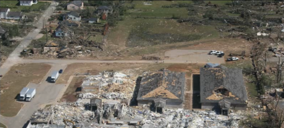 Close aerial view of the devastated school near University Blvd. The grass scouring within the streak of worst damage is consistent with a tornado of EF5 intensity, but the damage to the flattened school was deemed to be of high-end EF4 intensity due to the presence of undamaged light poles just south of the main building. (Image by Tim Marshall)