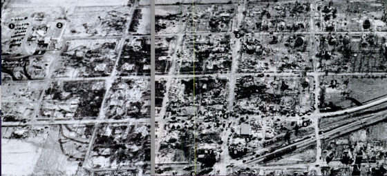 Composite aerial view of the town taken two days later after only moderate clean-up had occurred. The southern section of town (at left) was swept completely away, leaving a checkerboard of empty foundations. The rest of the community was left as a patchwork of F5 to F0 damage, with the least damage occurring in the northwest corner of town.