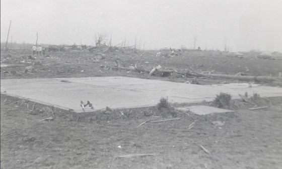 The remains of a home that was swept completely away by the tornado. Vegetation around the bare foundation was scoured from the ground, and the fallen tree trunk behind the home was debarked and stripped of branches. (Image by )