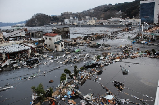 Severe damage to bay-front buildings in Kamaishi. A videographer in this area captured the entire sequence, which revealed that the first wave caused the majority of the damage and fatalities.