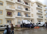 Vehicles piled beneath a damaged apartment building in Silves.